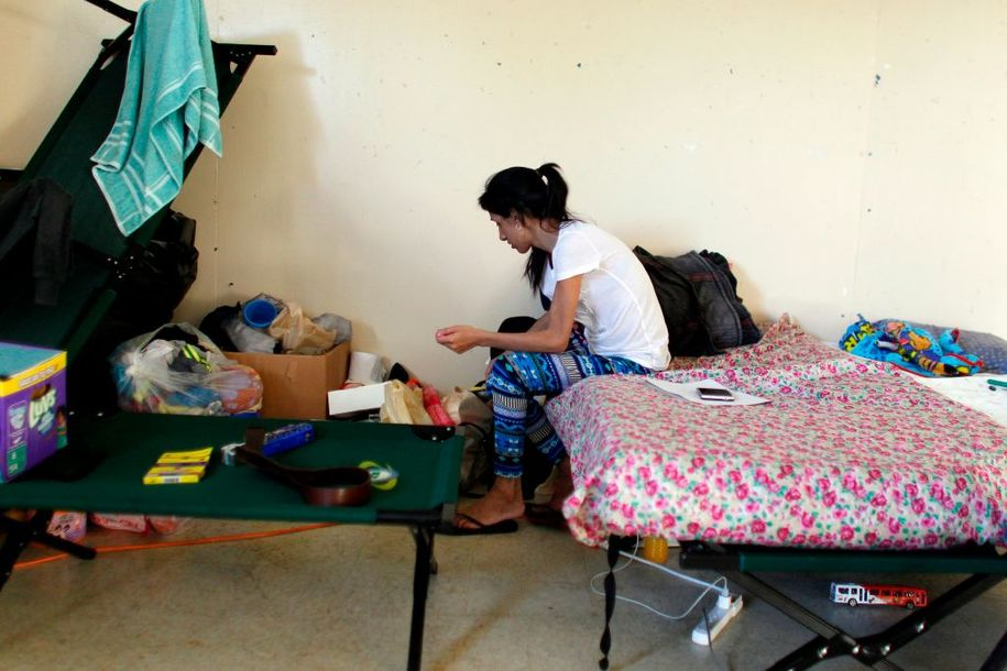 Elsa Diaz (27) looks through her belongings in a classroom turned bedroom in Barranquitas, Puerto Rico October 31, 2017..Twenty people from Barranquitas have been living for the past 42 days at the Luis Munoz Marin public school, a campus-turned-shelter in central Puerto Rico since Hurricane Maria damaged their homes while waiting for help to replace the homes they lost in the hurricane. / AFP PHOTO / Ricardo ARDUENGO        (Photo credit should read RICARDO ARDUENGO/AFP/Getty Images)