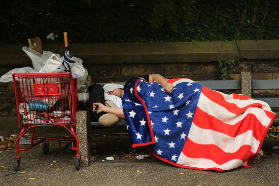 NEW YORK, NY - SEPTEMBER 10: A homeless man sleeps under an American Flag blanket on a park bench on September 10, 2013 in the Brooklyn borough of New York City. As of June 2013, there were an all-time record of 50,900 homeless people, including 12,100 homeless families with 21,300 homeless children homeless in New York City. (Photo by Spencer Platt/Getty Images)