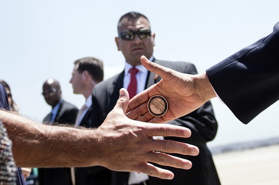 US President Barack Obama hands off a Presidential challenge coin after arriving at Marine Corps Air Station Miramar on May 8, 2014 near San Diego, California. Obama is on the second day of a three-day trip to California where he has largely been fundraising for Democrats. AFP PHOTO/Brendan SMIALOWSKI (Photo credit should read BRENDAN SMIALOWSKI/AFP/Getty Images)