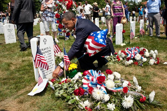 ARLINGTON, VA - MAY 30: In this handout from the White House, U.S. President Barack Obama lays a Presidential challenge coin on a grave in Section 60 at Arlington National Cemetery May 30, 2011 in Arlington, Virginia. (Photo by Pete Souza/White House via Getty Images)