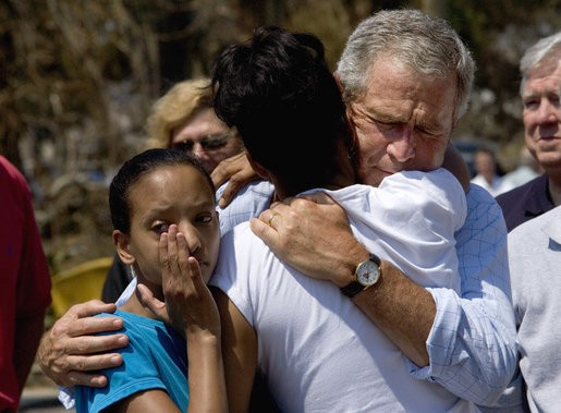 President George W. Bush comforts Bronwynne Bassier, right, and her sister Kim after landing in Biloxi, Miss., Friday Sept. 2, 2005, as part of his tour of the Hurricane Katrina-ravaged Gulf Coast. Their family lost everything in the wake of the devastating storm. https://commons.wikimedia.org/wiki/File:President_Bush_Biloxi_after_Katrina.jpg