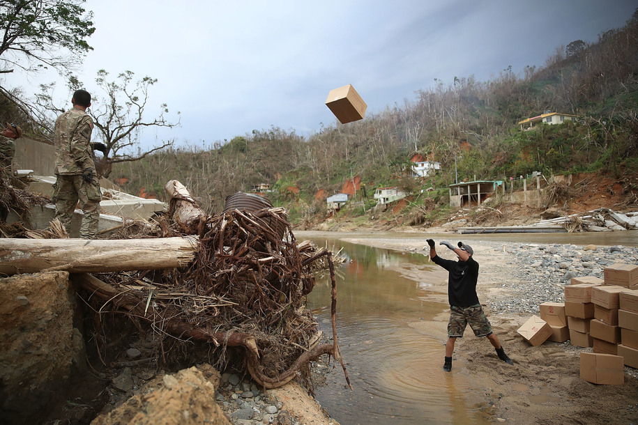 UTUADO, PUERTO RICO - OCTOBER 05: Daniel Braithwaite prepares to catch a box of M.R.E.'s as helps U.S. Army 1st Special Forces Command soldiers as they deliver food and water to people after Hurricane Maria swept through the island on October 5, 2017 in Utuado, Puerto Rico. The neighborhood was cut off from help for about 2 weeks and there is still a need for basic life necessities after the category 4 hurricane, passed through. (Photo by Joe Raedle/Getty Images)