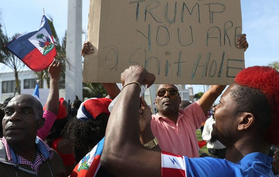 WEST PALM BEACH, FL - JANUARY 15: (EDITORS NOTE: Caption contains profanity.) People join together, near the Mar-a-Lago resort where President Donald Trump spent the last few days, to condemn President Trumps reported statement about immigrants from Haiti and to ask that he apologize to them on January 15, 2018 in West Palm Beach, Florida. President Trump is reported to have called Haiti, Africa and El Salvador places Òshithole countriesÓ last week, whose inhabitants are not desirable for U.S. immigration. (Photo by Joe Raedle/Getty Images)