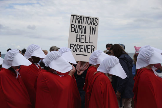 PALM BEACH, FL - JANUARY 20: People dressed as handmaidens protest against President Donald Trump on the one year anniversary of his inauguration on January 20, 2018 in Palm Beach, Florida. The protesters marched to a checkpoint near President Donald Trump's Mar-a-Lago estate as they joined thousands of people around the United States on the anniversary of TrumpÕs inauguration to state their opposition to him and his policies. (Photo by Joe Raedle/Getty Images)