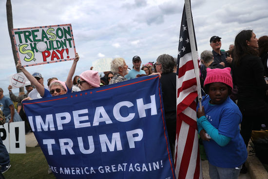 PALM BEACH, FL - JANUARY 20: People protest against President Donald Trump on the one year anniversary of his inauguration on January 20, 2018 in Palm Beach, Florida. The protesters marched to a checkpoint near President Donald Trump's Mar-a-Lago estate as they joined thousands of people around the United States on the anniversary of TrumpÕs inauguration to state their opposition to him and his policies. (Photo by Joe Raedle/Getty Images)