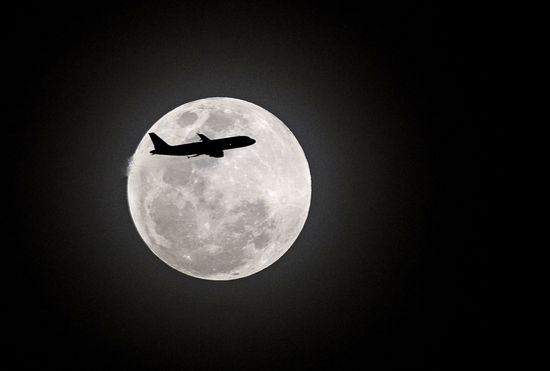 TOPSHOT - A commercial plane flies in the sky as a full moon is seen in Manila on January 31, 2018. .Skywatchers were hoping for a rare lunar eclipse that combines three unusual events ---a blue moon, a super moon and a total eclipse, which was to make for a large crimson moonviewable in many corners of the globe. / AFP PHOTO / NOEL CELIS        (Photo credit should read NOEL CELIS/AFP/Getty Images)