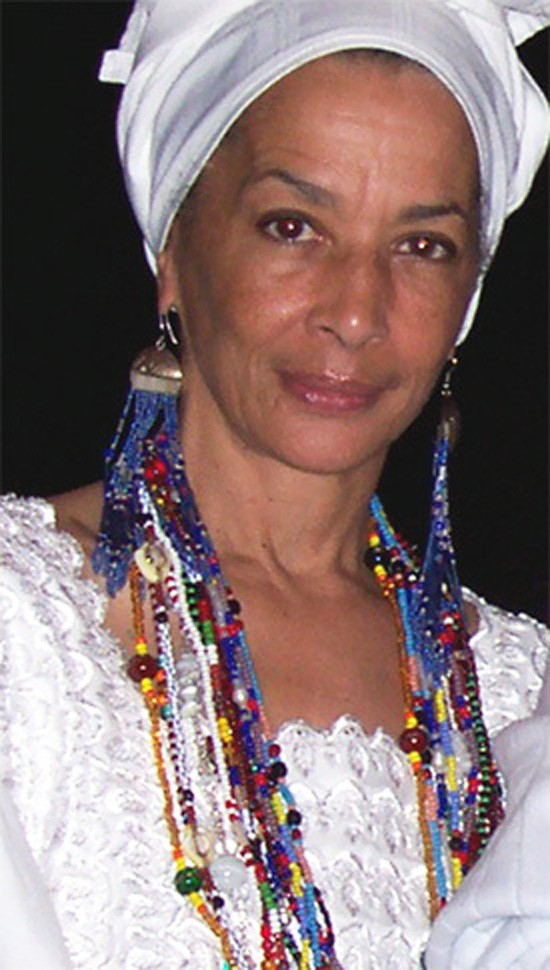 Denise Oliver Velez in Lucumi Santeria ritual attire -dressed in white, head wrapped and wearing elekes - bead necklaces