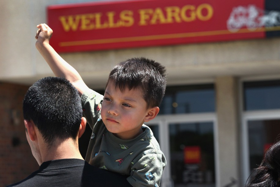 """AURORA, CO - JULY 01:  Ricky Torrez, 3, raises his fist with fellow demonstrators staging a protest outside a Wells Fargo bank branch on July 1, 2011 in Aurora, Colorado. A coalition of immigrant advocacy groups staged a """"national day of action"""" march to Wells Fargo branches. They say that Wells Fargo is a major shareholder in the private prison company GEO Group, Inc, which houses thousands of undocumented immigrants, many scheduled for deportation by the U.S. Immigration and Customs Enforcement agency, (ICE). The rights groups called on bank clients to close their Wells Fargo bank accounts in protest.  (Photo by John Moore/Getty Images)"""