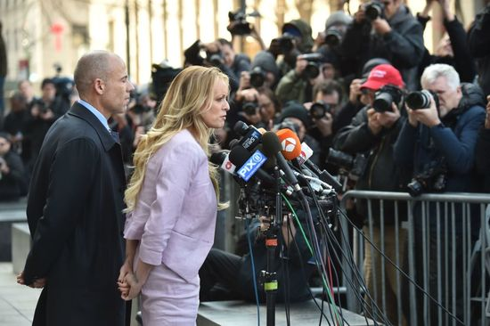 Adult-film actress Stephanie Clifford, (C) also known as Stormy Daniels speaks to the media next to her lawyer Michael Avenatti, after a court hearing outside the US Courthouse in New York on April 16, 2018..President Donald Trump's personal lawyer Michael Cohen has been under criminal investigation for months over his business dealings, and FBI agents last week raided his home, hotel room, office, a safety deposit box and seized two cellphones. / AFP PHOTO / Hector RETAMAL (Photo credit should read HECTOR RETAMAL/AFP/Getty Images)