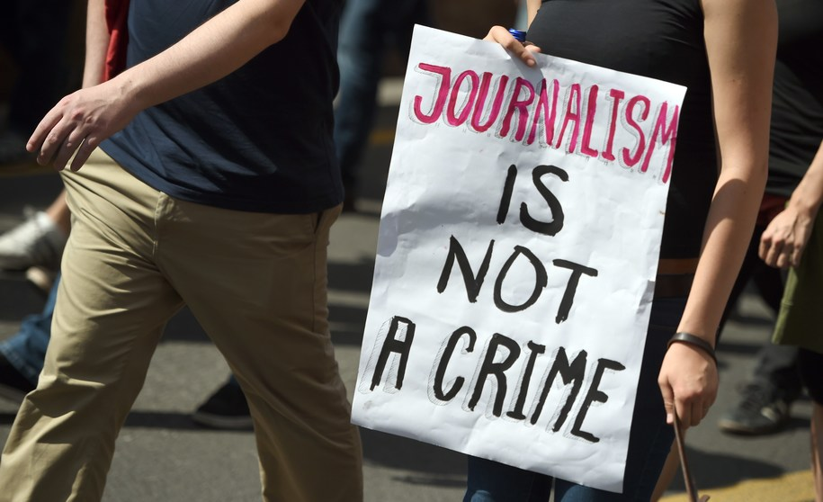 "FILES - Protester holds a poster written ""Journalism in not a crime"" during a demonstration in support of freedom of press on August 1, 2015, in Berlin as reaction to treason investigation against two writers of the news blog Netzpolitik. A clash between Germany's chief prosecutor and justice minister broke into the open on August 4, 2015, sparked by a treason probe against a blog that had published domestic security documents. The case centres of the blog Netzpolitik.org (Net politics), which earlier his year published documents on plans by Germany's domestic security agency to step up Internet surveillance.  AFP PHOTO / DPA / BRITTA PEDERSEN +++ GERMANY OUT        (Photo credit should read BRITTA PEDERSEN/AFP/Getty Images)"