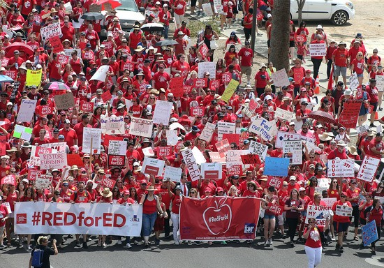 PHOENIX, AZ - APRIL 26:  Arizona teachers march through downtown Phoenix on their way to the State Capitol on April 26, 2018 in Phoenix, Arizona. Teachers state-wide staged a walkout strike on Thursday in support of better wages and state funding for public schools.  (Photo by Ralph Freso/Getty Images)