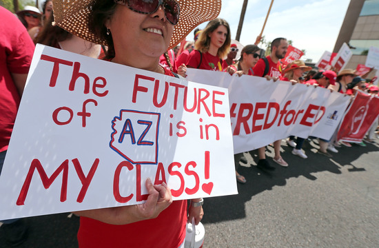 PHOENIX, AZ - APRIL 26:  Arizona teachers march toward the State Capitol as part of a rally for the #REDforED movement on April 26, 2018 in Phoenix, Arizona. Teachers state-wide staged a walkout strike on Thursday in support of better wages and state funding for public schools.  (Photo by Ralph Freso/Getty Images)