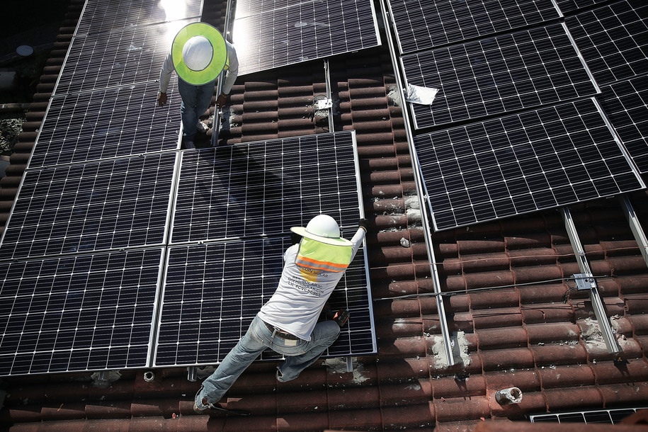 Roger Garbey and Andres Hernandez (L-R), from the Goldin Solar company, install a solar panel system on the roof of a home a day after the Trump administration announced it will impose duties of as much as 30 percent on solar equipment made abroad on January 23, 2018 in Palmetto Bay, Florida. (Photo by Joe Raedle/Getty Images)