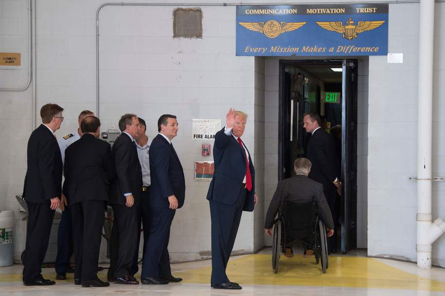 US President Donald Trump (2nd R) waves as he arrives with US Senator Ted Cruz (4th L), R-Texas, and Texas Governor Greg Abbott (R) at Ellington Field Joint Reserve Base in Houston, Texas, on May 31, 2018, to meet with those affected by the Santa Fe high school shooting. (Photo by JIM WATSON / AFP)        (Photo credit should read JIM WATSON/AFP/Getty Images)