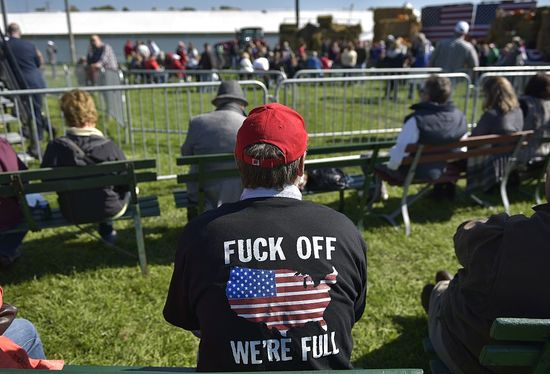 """An attendee wears a t-shirt with a message for would-be migrants at the 1st Congressional District Republican Party of Wisconsin Fall Fest on October 8, 2016 at the Walworth County Fairgrounds in Elkhorn, Wisconsin..Trump was scheduled to attend the Fall Fest with House Speaker Paul Ryan, who said he was """"sickened"""" by lewd and misogynistic comments Trump made as he described groping women in a 2005 video released Friday, disinviting him from a political event in Wisconsin. / AFP / MANDEL NGAN (Photo credit should read MANDEL NGAN/AFP/Getty Images)"""