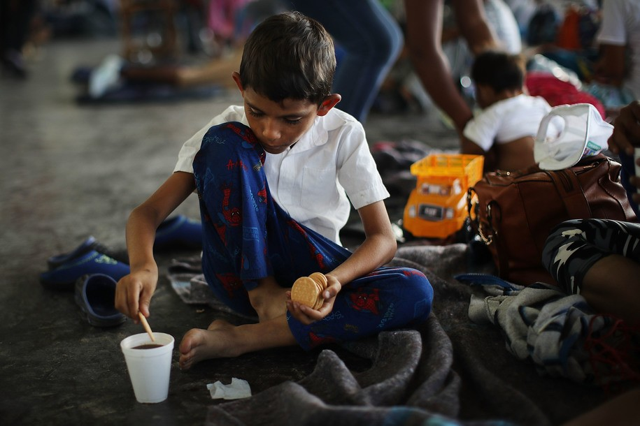 JUCHITAN DE ZARAGOZA, MEXICO - OCTOBER 30: A child, one of thousands of Central American migrants in the caravan, eats while in a camp for the evening on October 30, 2018 in Juchitan de Zaragoza, Mexico. Following a break on Sunday, the migrants, many of them fleeing violence in their home countries, resumed their march towards the United States border. As fatigue from the heat, distance and poor sanitary conditions has set in, the numbers of people participating in the march has slowly dwindled but a significant group are still determined to get to the United States. It has been widely reported that the Pentagon will deploy 5,200 active-duty troops to the U.S.-Mexico border in an effort to prevent members of the migrant caravan from illegally entering the country. (Photo by Spencer Platt/Getty Images)