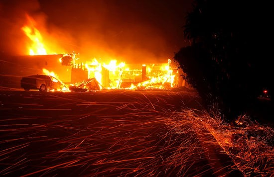 PARADISE, CA - NOVEMBER 08:  Embers blow in the wind as the Camp Fire burns a KFC restaurant on November 8, 2018 in Paradise, California. Fueled by high winds and low humidity, the rapidly spreading wildfire has ripped through the town of Paradise, charring 18,000 acres and destroying dozens of homes in a matter of hours. The fire is currently at zero containment. (Photo by Justin Sullivan/Getty Images)