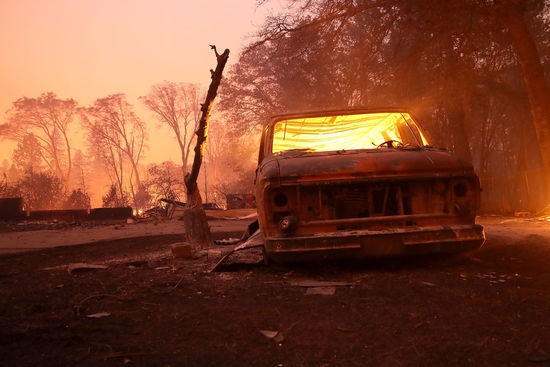 PARADISE, CA - NOVEMBER 08:  A burned out van continues to smolder after the Camp Fire moved through the area on November 8, 2018 in Paradise, California. Fueled by high winds and low humidity, the rapidly spreading wildfire has ripped through the town of Paradise, charring 18,000 acres and destroying dozens of homes in a matter of hours. The fire is currently at zero containment. (Photo by Justin Sullivan/Getty Images)