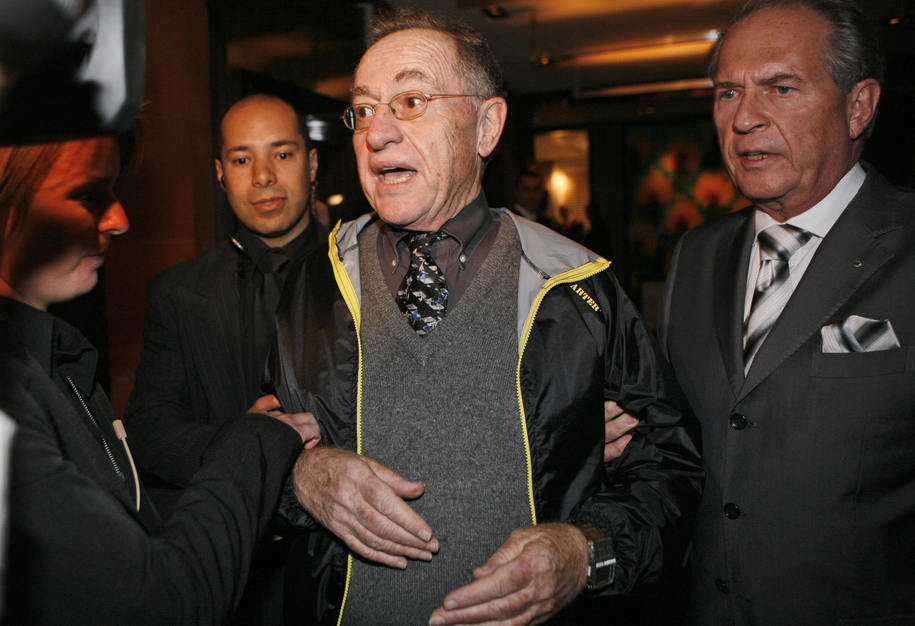 Harvard law professor Alan Dershowitz, (C), is led away after declaring he planned to challenge Iranian President Mahmoud Ahmadinejad about his views on the Holocaust and Israel minutes before the meeting with Swiss President Hans-Rudolf Merz and Iranian President Ahmadinejad in Geneva, Switzerland, on April 19, 2009. The United Nations opens its first global racism conference in eight years tomorrow with the US and at least five other countries boycotting the event out of apparent concern that Islamic countries will demand that it denounce Israel and ban criticism of Islam. AFP PHOTO / POOL / Anja Niedringhaus (Photo credit should read ANJA NIEDRINGHAUS/AFP/Getty Images)