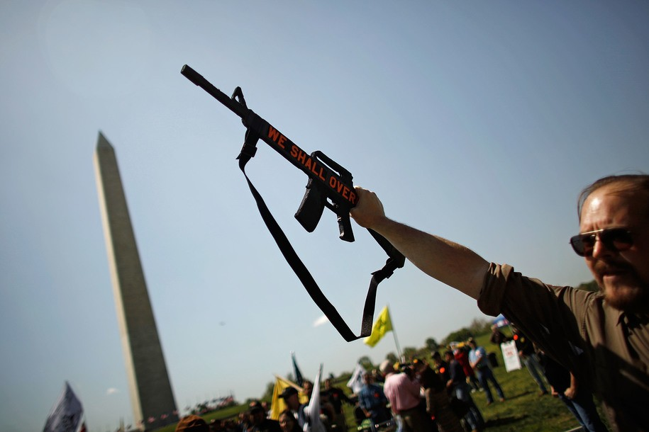 "WASHINGTON - APRIL 19:  A man identifying himself only as ""Colonel Hurtz"" holds up a mock gun made from foam core and shouts ""Wolverines!"" while joining about 500 pro-gun demonstrators near the Washington Monument April 19, 2010 in Washington, DC. Known as Patriots' Day, April 19 is also the anniversary of the American Revolutionary War battles of Lexington and Concord, the Oklahoma City bombing and the attack of the Branch Dividian compound.  (Photo by Chip Somodevilla/Getty Images)"