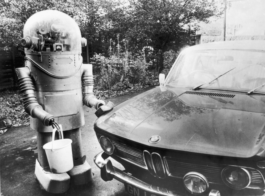 circa 1975:  A robot, holding a bucket and sponge, washes a car.  (Photo by Central Press/Getty Images)