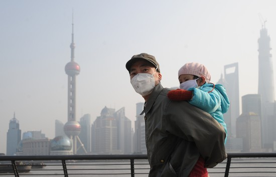 SHANGHAI, CHINA - DECEMBER 25:  (CHINA OUT) A man and his child wear masks as they visit The Bund on December 25, 2013 in Shanghai, China. Heavy smog covered many parts of China on Christmas Eve, worsening air pollution.  (Photo by VCG/VCG via Getty Images)
