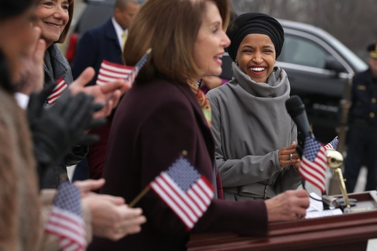WASHINGTON, DC - MARCH 08:  Rep. Ilhan Omar (D-MN) (R) listens to Speaker of the House Nancy Pelosi (D-CA) during a rally for H.R. 1, or the We The People Act, on the East Steps of the U.S. Capitol March 08, 2019 in Washington, DC. With almost zero chance of passing the Senate, H.R. 1 is a package of legislation aimed at bolstering voting rights, reducing corruption in Washington and overhauling the campaign finance system in an effort to reduce the influence of 'special interests.' (Photo by Chip Somodevilla/Getty Images)
