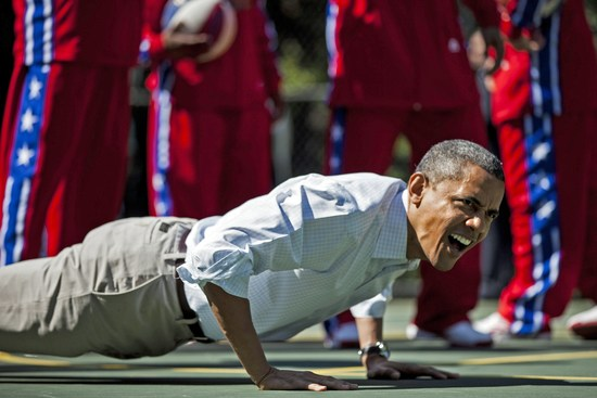 US President Barack Obama does pushups during backetball shooting drills during the annual Easter Egg Roll on the South Lawn of the White House April 9, 2012 in Washington, DC.  The First Family participated in the yearly event where the South Lawn is opened up to guests to participate in various egg rolls and other activities.  AFP PHOTO/Brendan SMIALOWSKI        (Photo credit should read BRENDAN SMIALOWSKI/AFP/Getty Images)