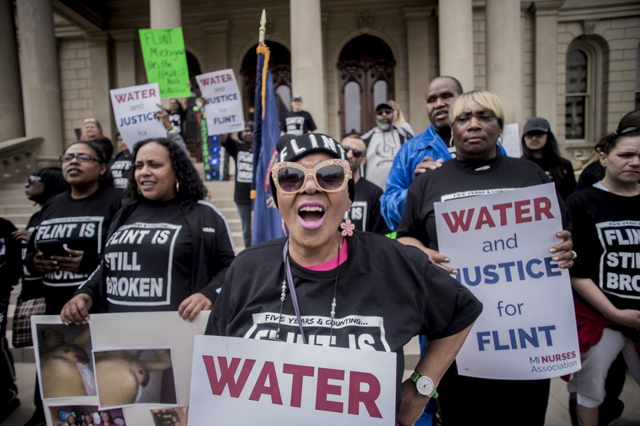 "Flint resident Freddie Fisher shouts out ""No justice, no peace!"" as she joins more than 50 Flint residents who rally on the five-year anniversary of the Flint water crisis at the Capitol Building on Thursday, April 25, 2019, in Lansing, Mich. Fisher said she's been afraid of interaction with the water, so much to the point that she has to force herself to take a bath to keep clean, but not without its fears of what it could do to her body. She erupted with an impassioned speech asking for politicians to step up and continue to aid the city's residents until the issue is fully resolved. (Jake May/MLive.com/The Flint Journal via AP)"