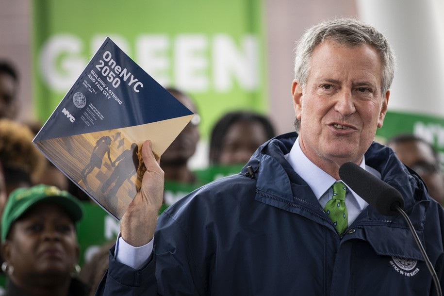 NEW YORK, NY - APRIL 22: New York City Mayor Bill de Blasio holds up a copy of 'One NYC 2050' as he speaks the city's response to climate change at Hunters Point South Park, April 22, 2019 in the Queens borough of New York City. The Climate Mobilization Act passed the city council on last Thursday with a vote of 45 to 2.Two tenants of the city's 'Green New Deal' include a requirement that the city to switch entirely to renewable energy within five years and requiring private building owners to cut their emissions by 30 percent by 2030. (Photo by Drew Angerer/Getty Images)