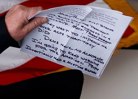 """CROPPED: In this May 22, 2019, photo, President Donald Trump carries notes that say """"they want to impeach me"""" as he walks from the Oval Office to speak in the Rose Garden of the White House in Washington. (AP Photo/Evan Vucci)"""