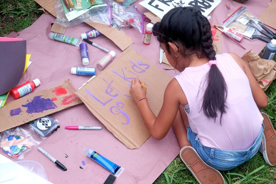 Linda Alonso, 8, paints a sign during a protest rally and vigil in support of the liberation and reunification of migrant children outside the Homestead Temporary Shelter for Unaccompanied Children, in Homestead, Florida, on July 12, 2019. (Photo by GASTON DE CARDENAS / AFP) (Photo credit should read GASTON DE CARDENAS/AFP/Getty Images)
