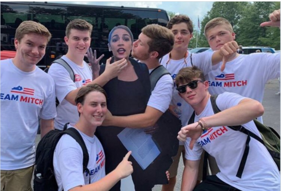 "Young men in ""Team Mitch"" shirts posing as they grope and choke a cardboard cut-out of Rep. Alexandria Ocasio-Cortez"