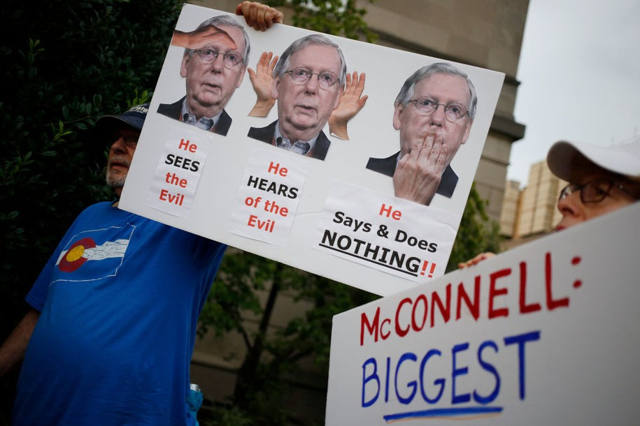 LOUISVILLE, KY - AUGUST 06: Activists hold signs while demonstrating outside the office of Senate Majority Leader Mitch McConnell (R-KY) on August 6, 2019 in Louisville, Kentucky. Protestors from Kentucky March For Our Lives held a candlelight vigil and called on McConnell to pass legislation expanding background checks for firearms purchases in the wake of shootings in El Paso, Texas and Dayton, Ohio. (Photo by Luke Sharrett/Getty Images)