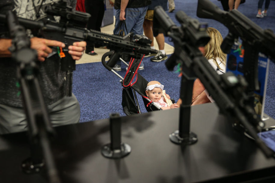 A baby looks up at a firearms display in an exhibit hall at the Kay Bailey Hutchison Convention Center during the NRA's annual convention on May 6, 2018 in Dallas, Texas. (Photo by Loren ELLIOTT / AFP)        (Photo credit should read LOREN ELLIOTT/AFP/Getty Images)