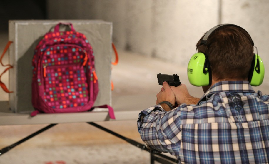 SALT LAKE CITY, UT - DECEMBER 21: Chief Operating Officer for Amendment II, Rich Brand, shoots a child's backpack with their Rynohide CNT Shield in it on December 21, 2012 in Salt Lake City, Utah. Their orders for the bulletproof shield have gone up dramatically since the school shooting in Connecticut last week. (Photo by George Frey/Getty Images)