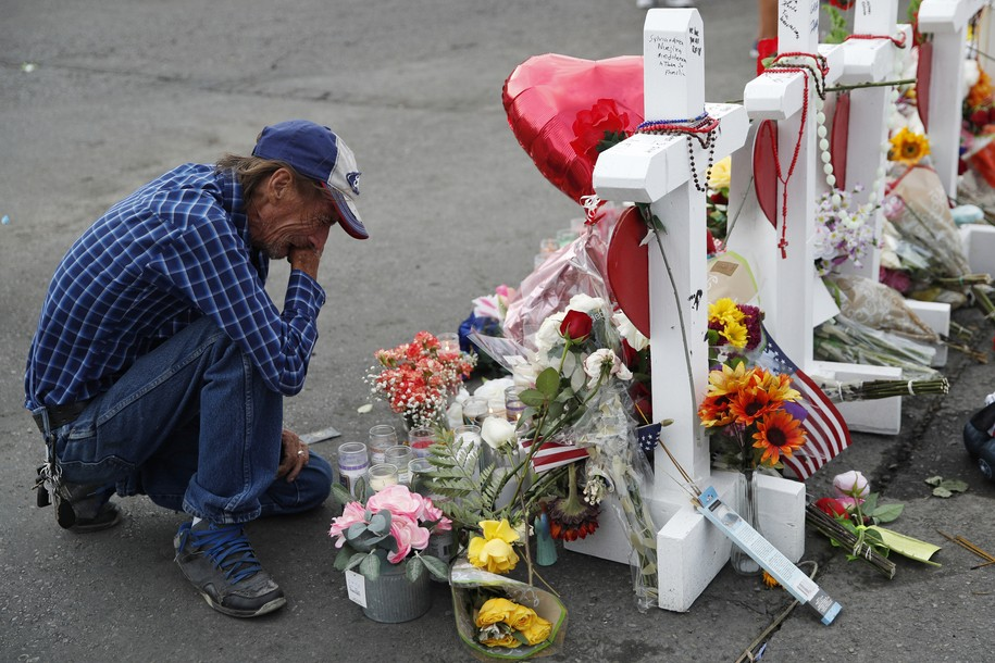 FILE - In this Aug. 6, 2019 file photo, Antonio Basco cries beside a cross at a makeshift memorial near the scene of a mass shooting at a shopping complex, in El Paso, Texas. Basco, whose 63-year-old wife was among the Texas mass shooting victims says he has no other family and welcomes anyone wanting to attend her services in El Paso. Margie Reckard was among 22 people fatally shot on Aug. 3 at a the Walmart. Reckard and Basco were married 22 years. (AP Photo/John Locher, File)
