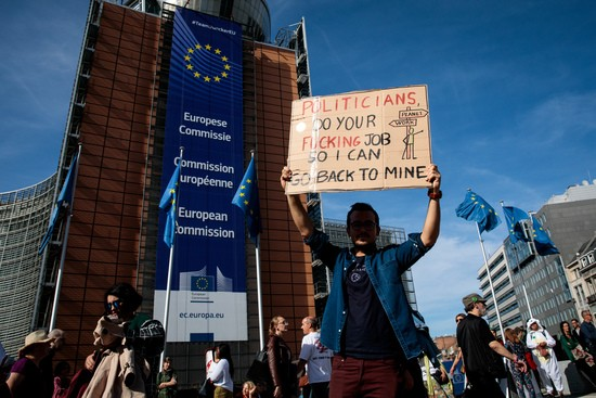 BRUSSELS, BELGIUM - SEPTEMBER 20: A protester holds up a placard outside the European Commission as hr takes part in a Global Climate Strike demonstration on September 20, 2019 in Brussels, Belgium. Millions of people join protests around the world today to mark the start of a week of global climate strikes, with activists calling on their Governments to urgently address the climate crisis. (Photo by Jack Taylor/Getty Images)