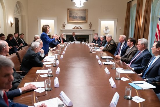 Nancy Pelosi stands pointing at at seated Donald Trump