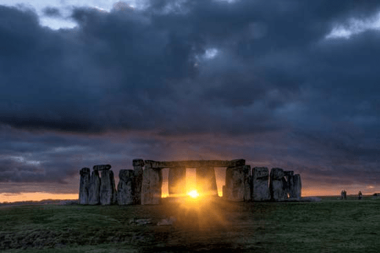 Winter solstice sun through Stonehenge with storm clouds overhead