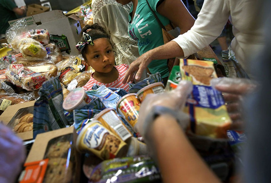 EGG HARBOR, NJ - AUGUST 28: Low-income residents select free bread and produce at the Community Food Bank of New Jersey on August 28, 2015 in Egg Harbor, New Jersey. The food bank has seen an 11 percent increase in food distribution in Atlantic County since four of Atlantic City's major casinos closed in 2014, laying of 8,000 people. The closures brought Atlantic City's unemployment rate to more than 11 percent, double the national average. The mass unemployment has produced the highest foreclosure rate of any metropolitan U.S. area, with 1 out of 113 homes now in foreclosure in Atlantic County. (Photo by John Moore/Getty Images)