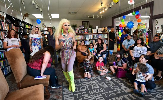 """Drag queens Athena Kills (C) and Scalene Onixxx arrive to awaiting adults and children for Drag Queen Story Hour at Cellar Door Books in Riverside, California on June 22, 2019. - Athena and Scalene, their long blonde hair flowing down to their sequined leotards and rainbow dresses, are reading to around 15 children at a bookstore in Riverside. The scene would be unremarkable -- except that they are both drag queens. The reading workshop is part of """"Drag Queen Story Hour,"""" an initiative launched in 2015 by a handful of libraries and schools across the United States. (Photo by Frederic J. BROWN / AFP)        (Photo credit should read FREDERIC J. BROWN/AFP via Getty Images)"""