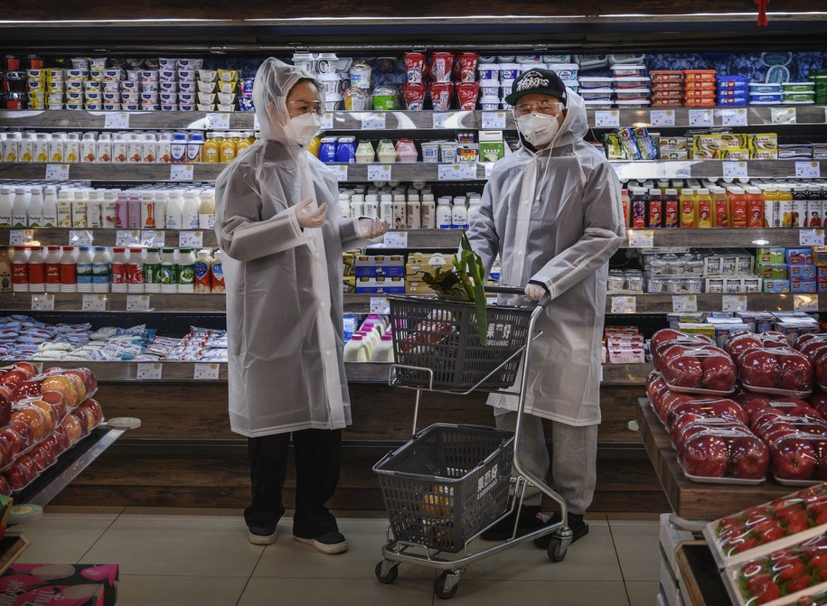 BEIJING, CHINA - FEBRUARY 11: A Chinese couple wear plastic coats and protective masks as they shop for groceries at a supermarket on February 11, 2020 in Beijing, China. The number of cases of a deadly new coronavirus rose to more than 42000 in mainland China Tuesday, days after the World Health Organization (WHO) declared the outbreak a global public health emergency. China continued to lock down the city of Wuhan in an effort to contain the spread of the pneumonia-like disease which medicals experts have confirmed can be passed from human to human. In an unprecedented move, Chinese authorities have put travel restrictions on the city which is the epicentre of the virus and municipalities in other parts of the country affecting tens of millions of people. The number of those who have died from the virus in China climbed to over 1000 on Tuesday, mostly in Hubei province, and cases have been reported in other countries including the United States, Canada, Australia, Japan, South Korea, India, the United Kingdom, Germany, France and several others. The World Health Organization has warned all governments to be on alert and screening has been stepped up at airports around the world. Some countries, including the United States, have put restrictions on Chinese travellers entering and advised their citizens against travel to China. (Photo by Kevin Frayer/Getty Images)