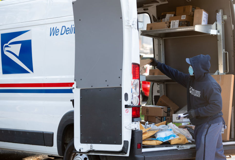 A mailman wearing a mask and gloves to protect himself and others from COVID-19, known as coronavirus, loads a postal truck with packages at a United States Postal Service (USPS) post office location in Washington, DC, April 16, 2020. - For many Americans, checking the mailbox is a daily ritual, a constant in a quickly changing world that can yield anything from wedding invitations to tax audits to new clothes..But as with many ordinary things as the coronavirus crisis unfolds, the US Postal Service -- already compromised by a mountain of debt -- has a most uncertain future. (Photo by SAUL LOEB / AFP) (Photo by SAUL LOEB/AFP via Getty Images)
