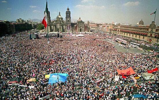 """MEXICO CITY, MEXICO:  A crowd of more than 150,000 people gather at the central Zocalo square 11 March 2001 before the Presidential Palace (BACKGROUND) in the Mexican capital at the conclusion of a two-week 3,000-kilometer (1,900-mile) Zapatista march to promote indigenous rights legislation. """"Subcomandante Marcos"""" was given a tumultuous welcome from the crowd, which had come to hear the charismatic leader of the Zapatista National Liberation Army (EZLN).  AFP PHOTO/ALFREDO ESTRELLA (Photo credit should read ALFREDO ESTRELLA/AFP via Getty Images)"""