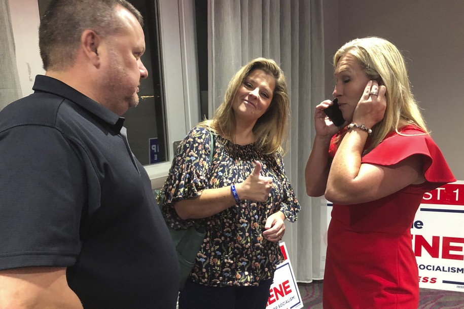 Construction executive Marjorie Taylor Greene, third from left, claps with her supporters at a watch party event, late Tuesday, Aug. 11, 2020, in Rome, Ga. Greene, criticized for promoting racist videos and adamantly supporting the far-right QAnon conspiracy theory, won the GOP nomination for northwest Georgia's 14th Congressional District. (AP Photo/Mike Stewart)