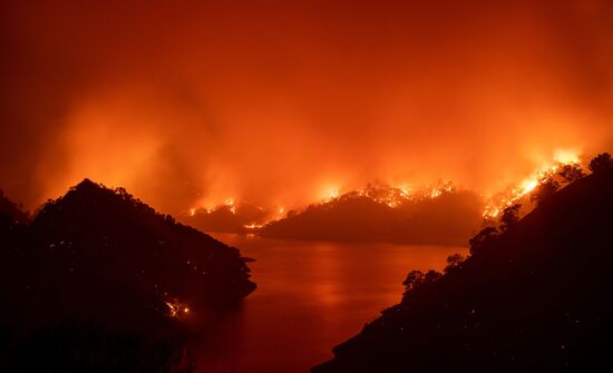TOPSHOT - Flames surround Lake Berryessa during the LNU Lightning Complex fire in Napa, California on August 19, 2020. - Thousands of people fled their homes in northern California on August 19 as hundreds of fast-moving wildfires spread across the region, burning houses and leading to the death of a helicopter pilot. (Photo by JOSH EDELSON / AFP) (Photo by JOSH EDELSON/AFP via Getty Images)