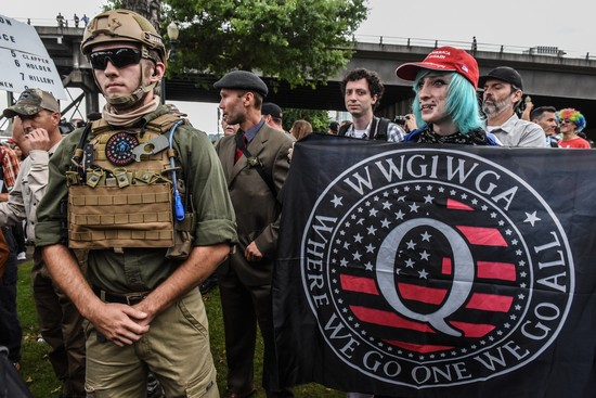PORTLAND, OR - AUGUST 17: A person holds a banner referring to the Qanon conspiracy theory during a alt-right rally on August 17, 2019 in Portland, Oregon. Anti-fascism demonstrators gathered to counter-protest a rally held by far-right, extremist groups. (Photo by Stephanie Keith/Getty Images)