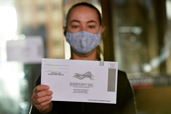 A woman holds up a mail-in ballot before dropping it off at Boston City Hall during the Massachusetts State Primary on September 1, 2020 in Boston, Massachusetts. (Photo by Joseph Prezioso / AFP) (Photo by JOSEPH PREZIOSO/AFP via Getty Images)