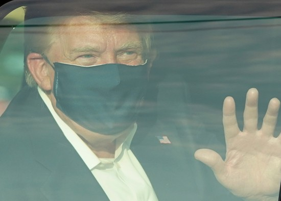 """TOPSHOT - A car with US President Trump drives past supporters in a motorcade outside of Walter Reed Medical Center in Bethesda, Maryland on October 4, 2020. - US President Donald Trump drove past supporters outside the hospital where he was being treated for Covid-19, after announcing on Twitter a """"suprise visit"""" to his backers. (Photo by ALEX EDELMAN / AFP) (Photo by ALEX EDELMAN/AFP via Getty Images)"""